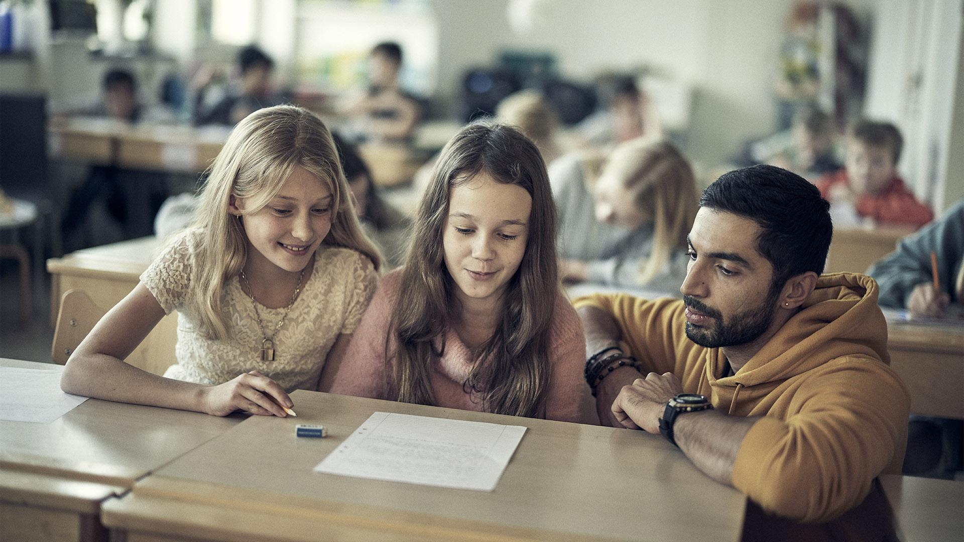 Lärare hjälper två elever på Noblaskolan